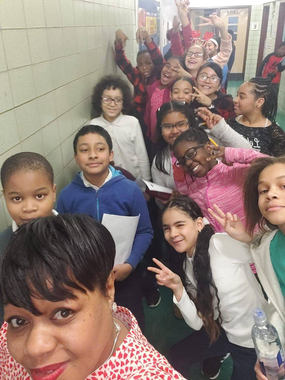 Ms. Nealy and her students pose playfully in the hallway for a class selfie.