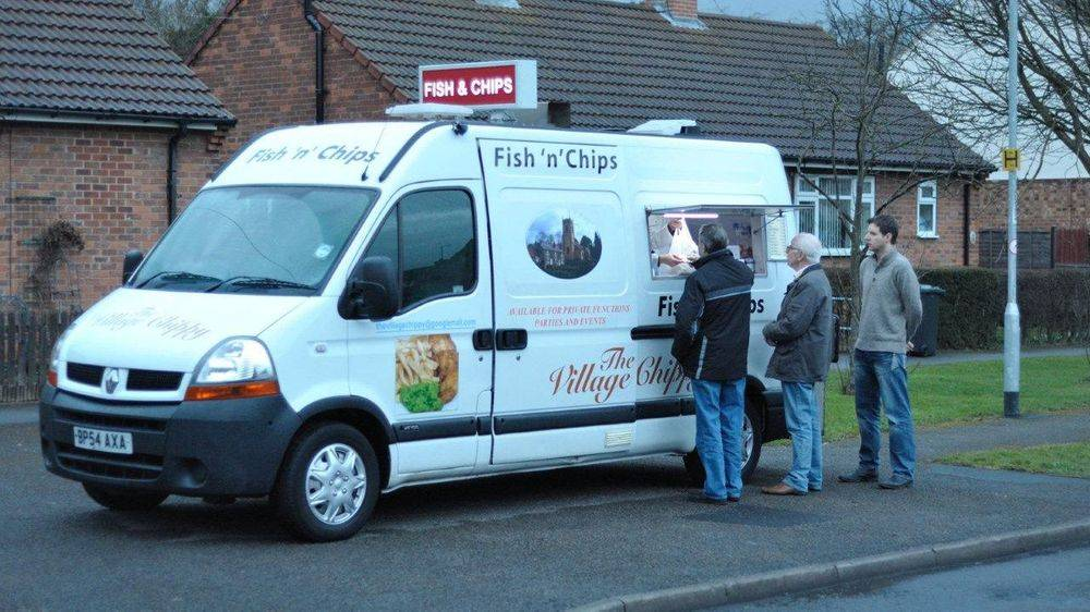 "Our pristine catering fish and chip van with a large illuminated red sign on the roof with ""Fish & Chips"" in white letters, serving a queue of customers on the street in Bramham."