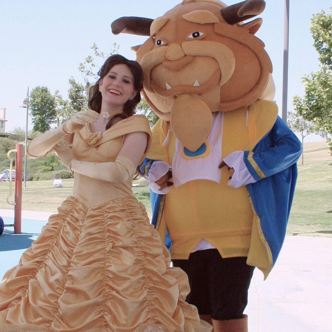 A princess & mascot beast posing in a park.