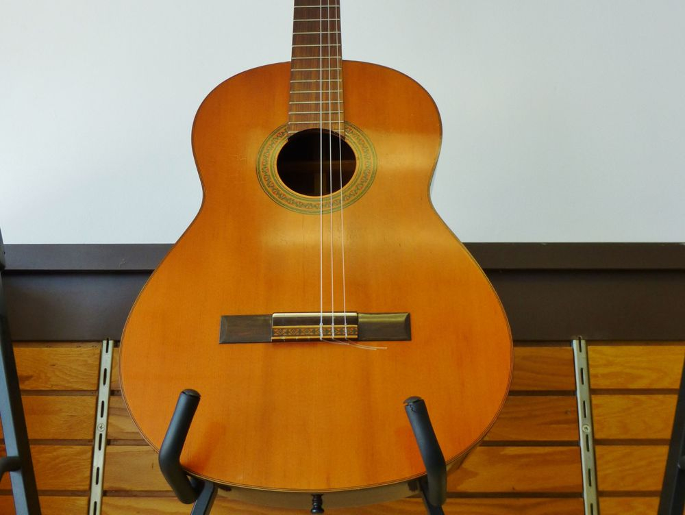 close up picture of a vintage Yamaha acoustic guitar on a stand