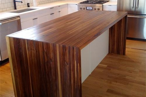 """Walnut edge grain """"waterfall' style counter top with overhang for stools,  White floating shelves"""