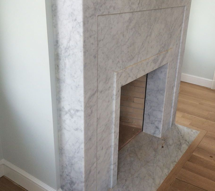honed White Carrara marble fireplace surround and hearth