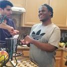 A happy blind young man is making cookies with his TVI and putting them on the cookie tray.