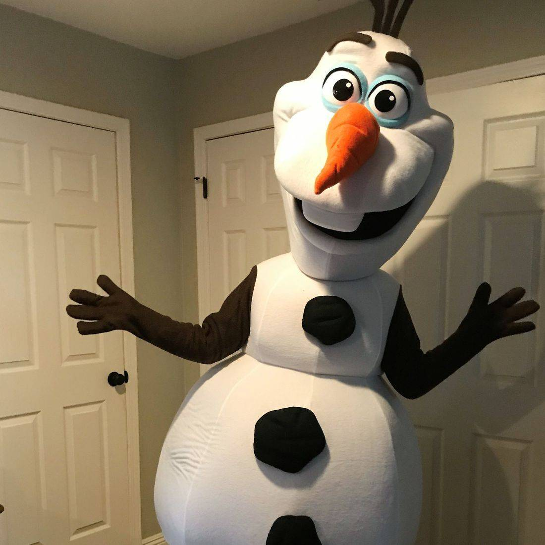 A white snowman costume with orange nose and brown arms smiling.
