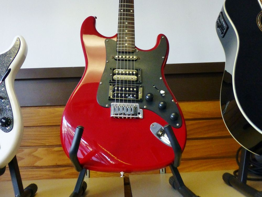 closeup picture of a red and black Hohner Arbor Electric Guitar on a Stand