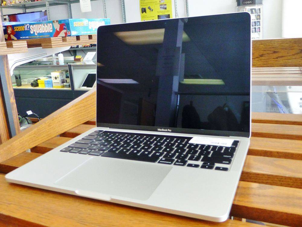 close up picture of a silver and black Apple MacBook Pro M1 laptop on a wooden shelf