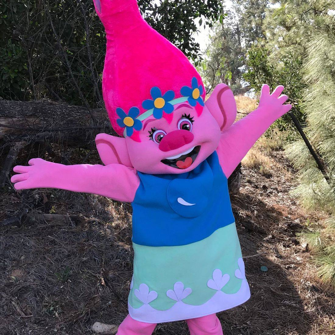 Pink troll character with arms wide open in the forest.