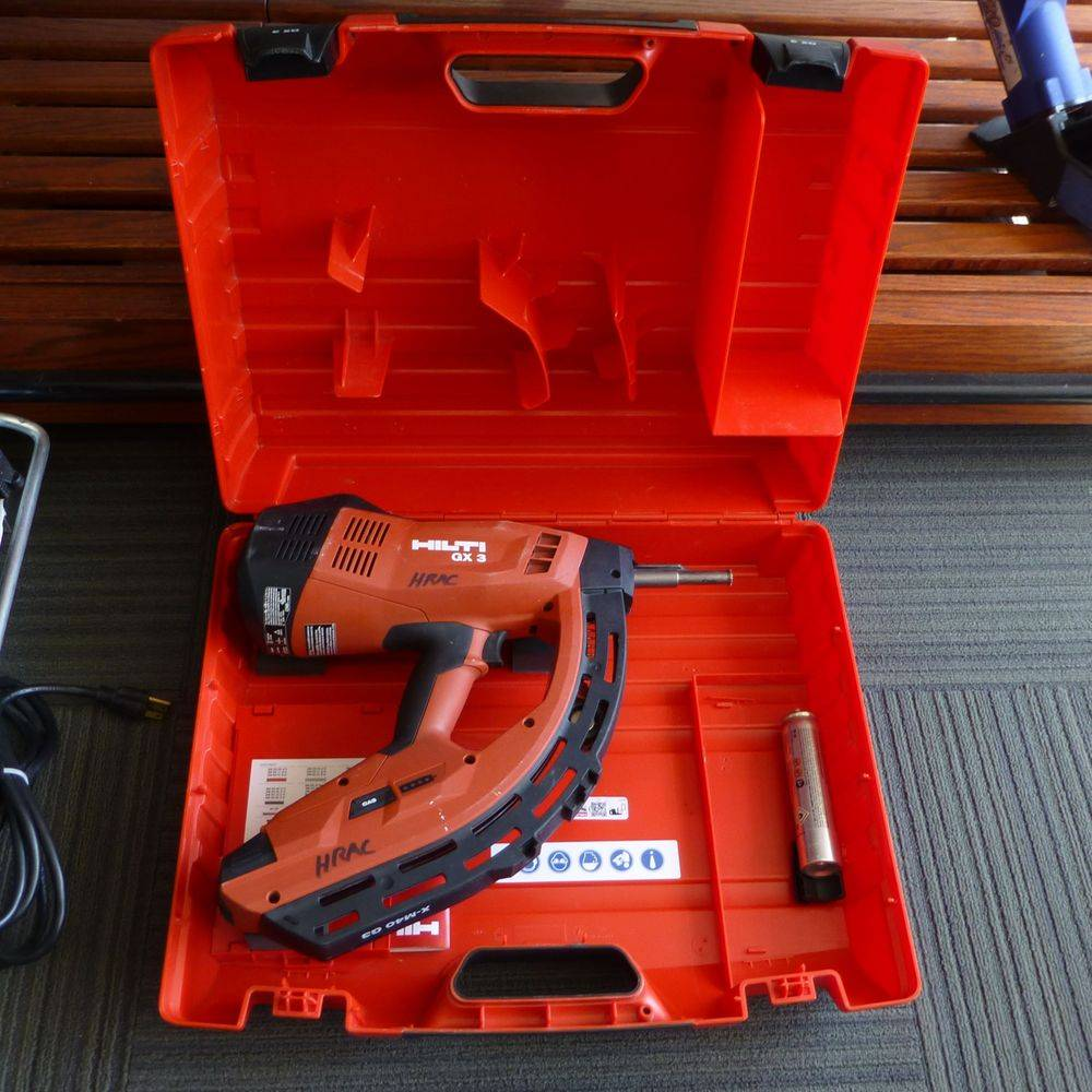 Red and Black hilti nail gun in red case on a wooden shelf