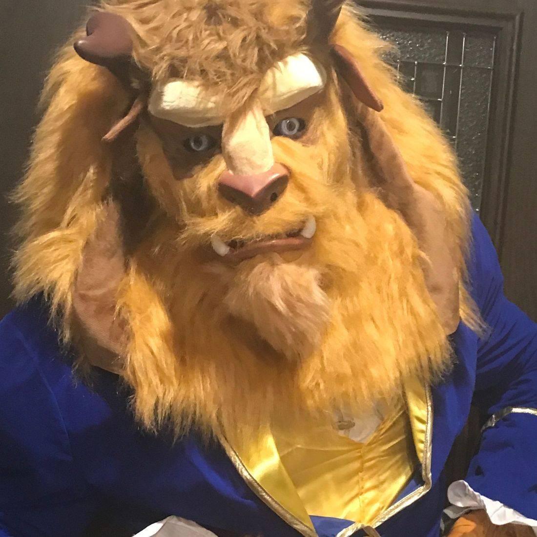 Furry monster beast in blue jacket in front of a door.