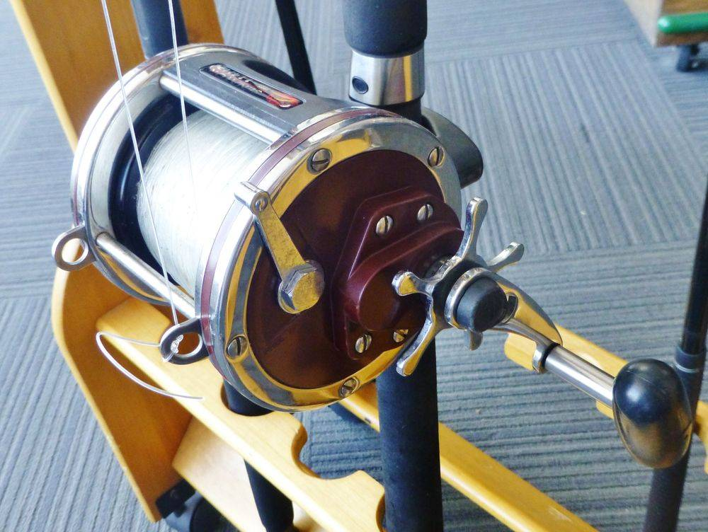 close up picture of Red and silver penn fishing reel on a fishing rod