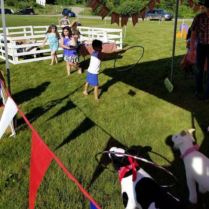 little boy throwing hoop over animals playing a  carnival game