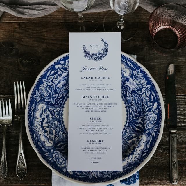 Overhead view of vintage blue floral and bird menu on toile plates at wedding head table