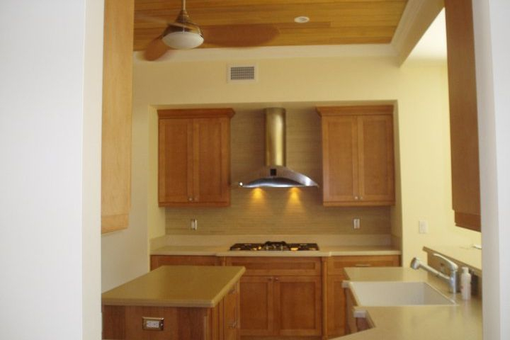 Delray Beach home custom kitchen cabinets, solid surface tops & stainless modern hood
