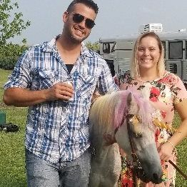 Man and woman standing next to a unicorn