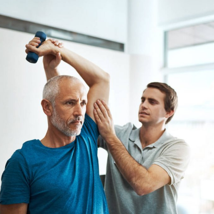 Man using weights guided by a Physiotherapist