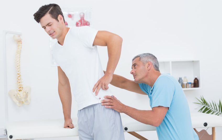 Chiropractor examining patient with back pain