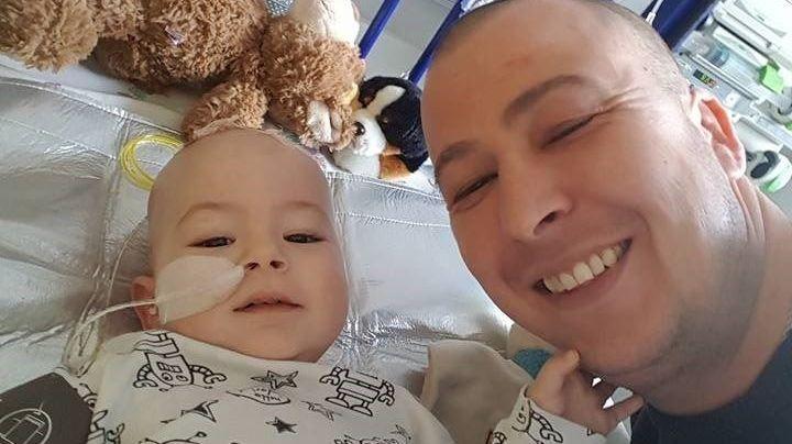 Kleinkind mit Versorgungsschlauch im Kinderbett, Kind und Vater lächelen in die Kamera