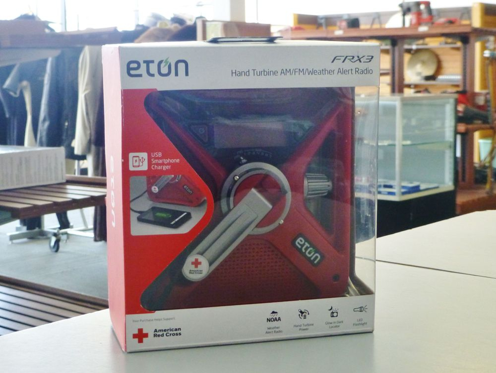 close up picture of a red Eton weather alert radio in the original box on top of a counter