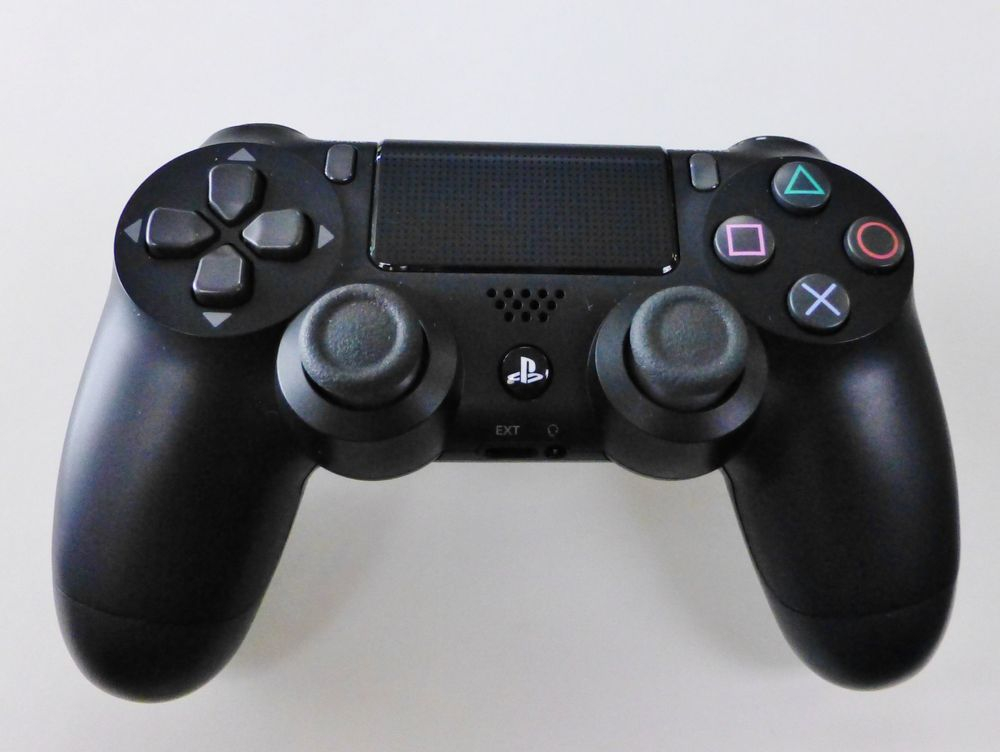 black sony PS4 wireless controller on a white background