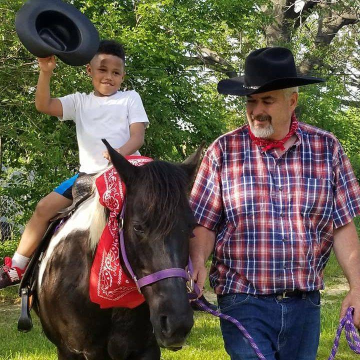 Boy holding cowboy hat in the air riding a pony led by a cowboy