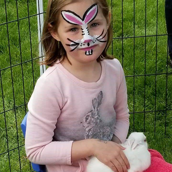 Little girl with bunny face paint holding a white bunny