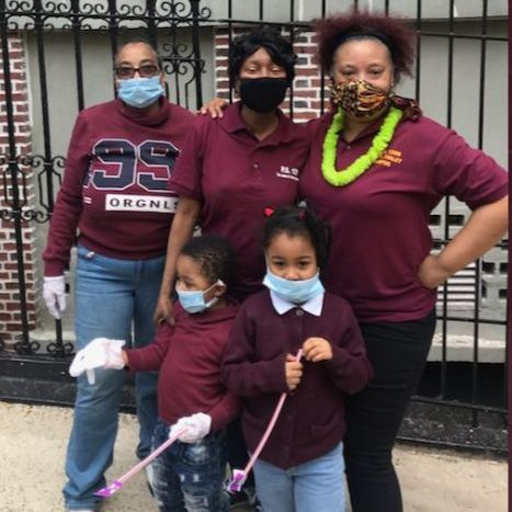 3 adults and 2 children from ps 129 pose for a photo.  All dressed in maroon shirts