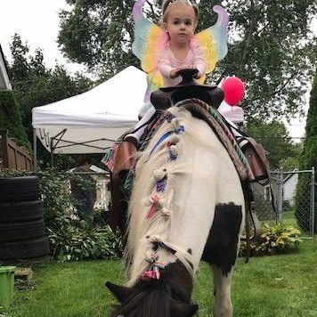 LITTLE GIRL SITTING ON PAINT PONY UNICORN