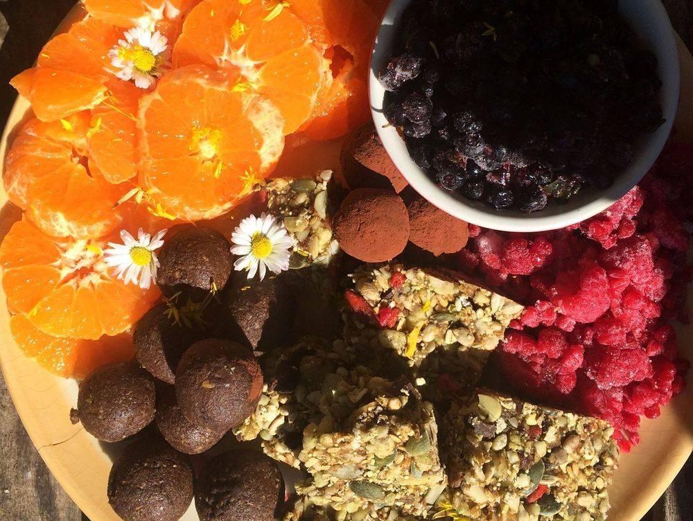 fresh orange slices with granola bars, raspberries and daisies