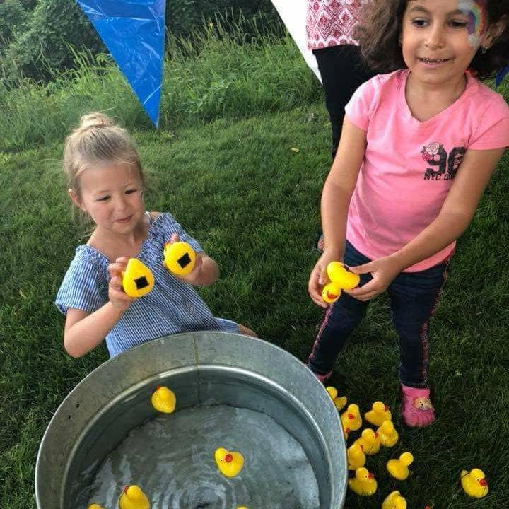 Little girls playing a game of duck pond - pick up two ducks and match shapes