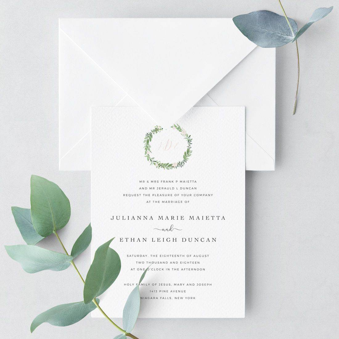 Simple modern invitation flat lay with eucalyptus, laurel wreath and monogram
