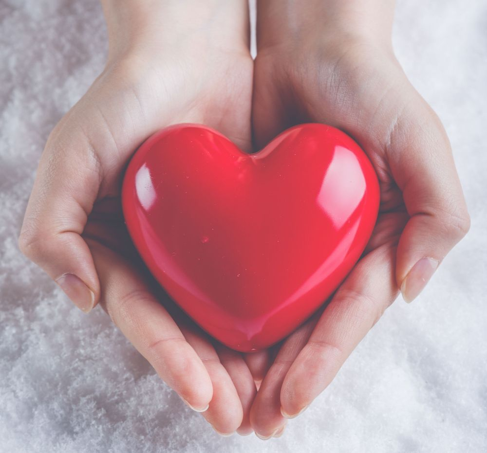A red heart being held in hands