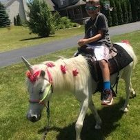 Little boy riding a white unicorn pony