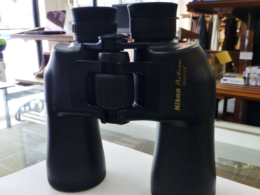 pair of black Nikon binoculars on a white paper