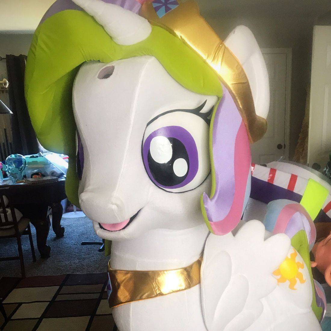 A white unicorn mascot character with rainbow colored hair.