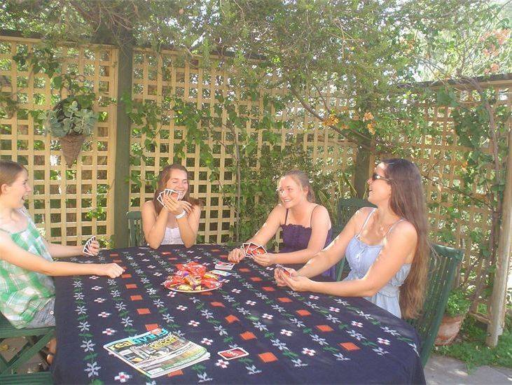 Girlfriends having fun playing cards in the courtyard and enjoying the fine weather.