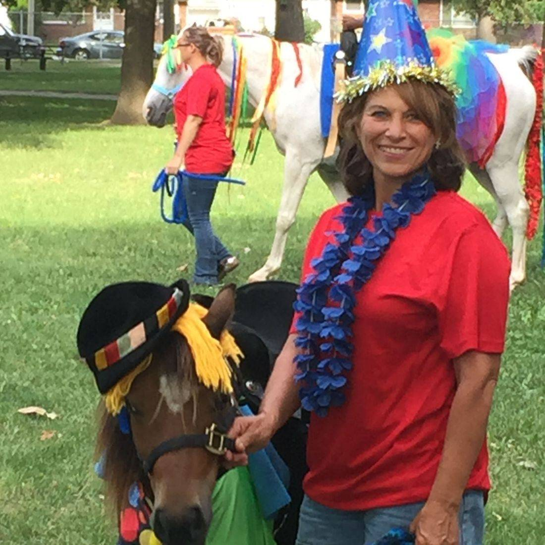 Pony dressed as a clown and a woman with a clown hat on