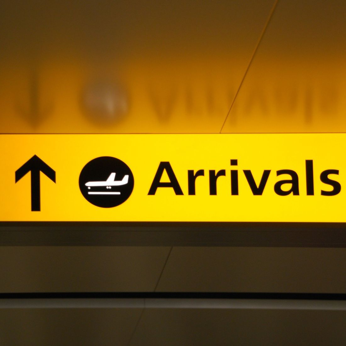 yellow airport arrivals sign with arrow