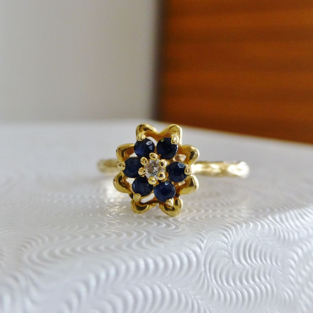 Closeup picture of a yellow gold flower ring with round blue sapphire petals and a diamond center
