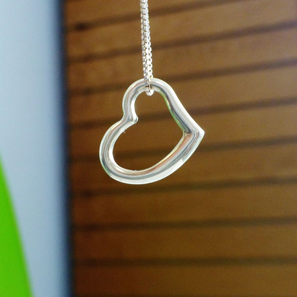 Closeup Picture of a Polished yellow gold open heart charm