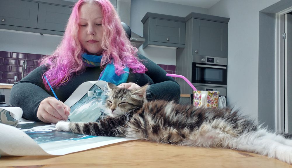 Helen Rutherford painting on her kitchen table. Her kitten is lying across her painting.