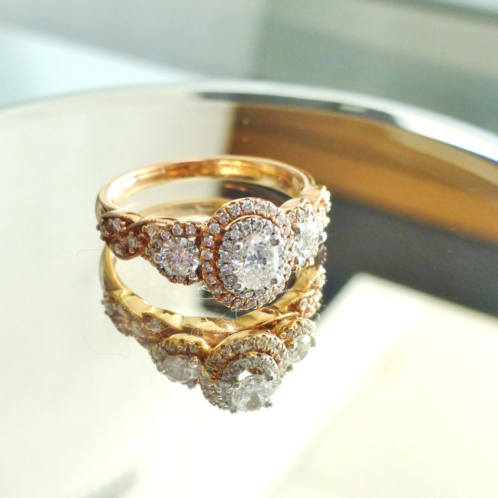 close up picture of a vintage inspired rose gold ring with a centered oval diamond double halo and side diamonds