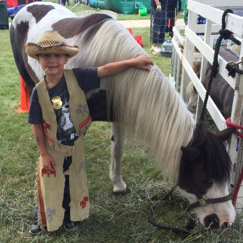 little boy dressed as a cowboy standing next to a horse