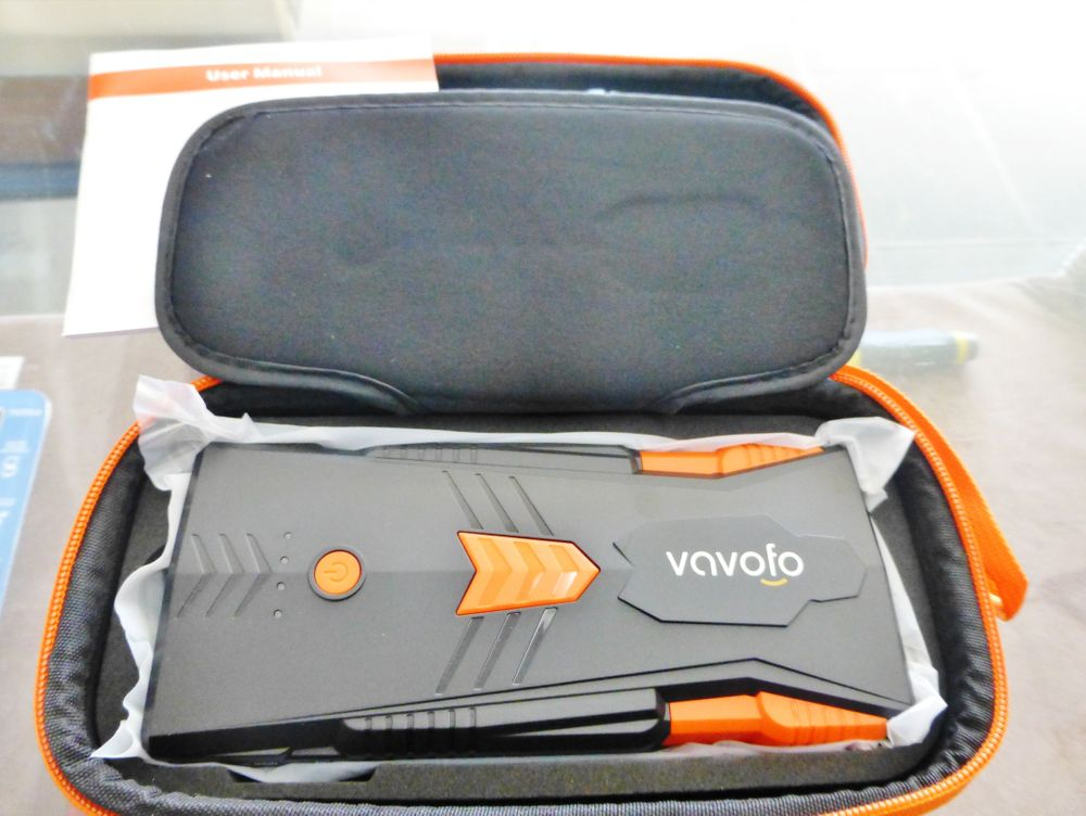 close up picture of an orange and black Vavofo jump starter powwer pack in a case