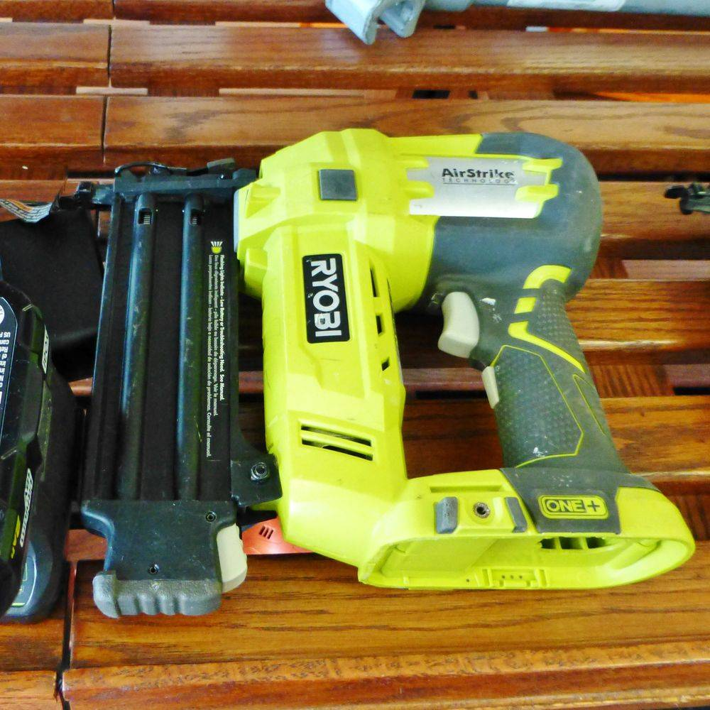 Closeup picture of a ryobi brad nailer with charger and battery