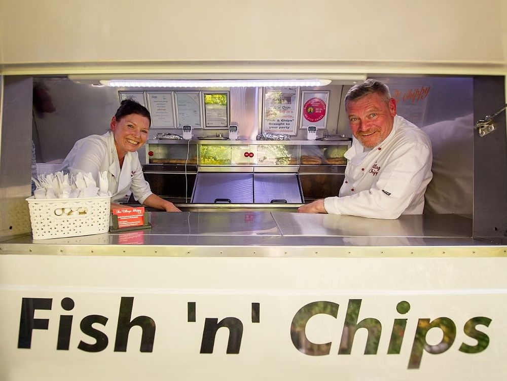 Owners Amanda and Garry in their chefs whites posing inside the fish and chip catering van through the serving hatch.