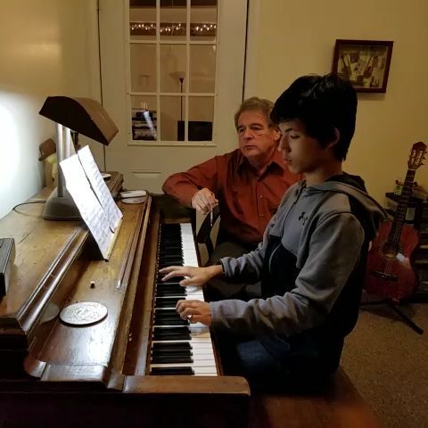 Michael O. in piano lessons with his music instructor, Ray Braselton.