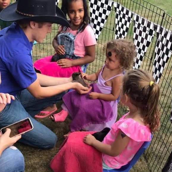 Children sitting in petting zoo holding bunnies