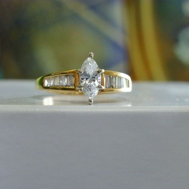Marquise Diamond Solitaire engagement ring with side baguette diamonds in yellow gold