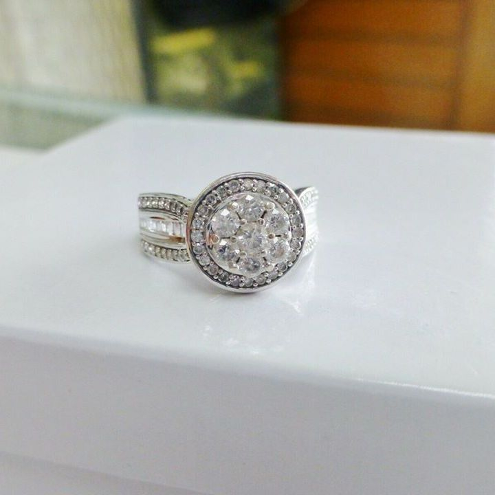 Round diamond cluster with a diamond halo and side baguette accents in a white gold engagement ring