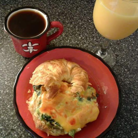 Luxury scrambeled eggs with spinach on a croissant with chicory coffee